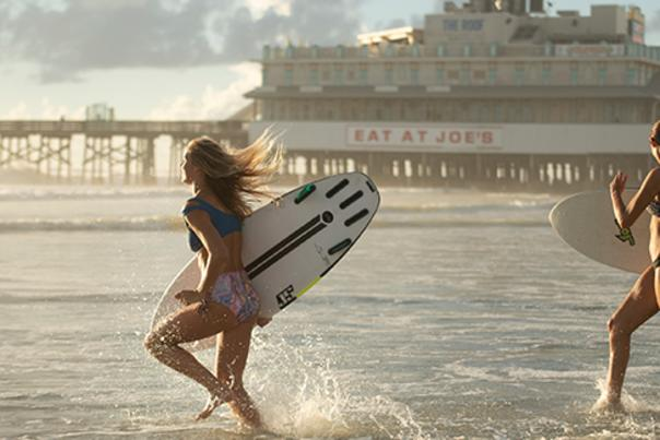 Two girls with surfboards run into the ocean by the Pier and Joe's Crab Shack.