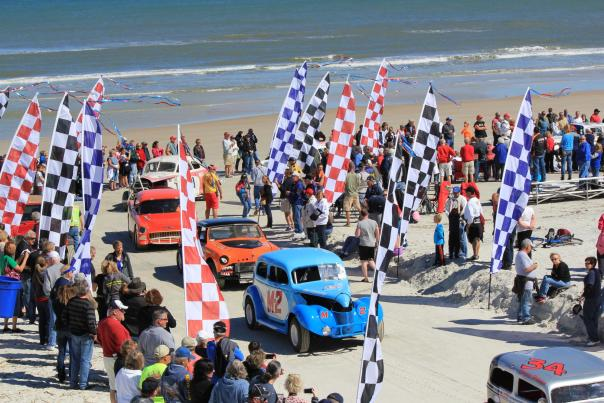 Former beach racing cars cross the finish line during the Historic North Turn Beach Parade