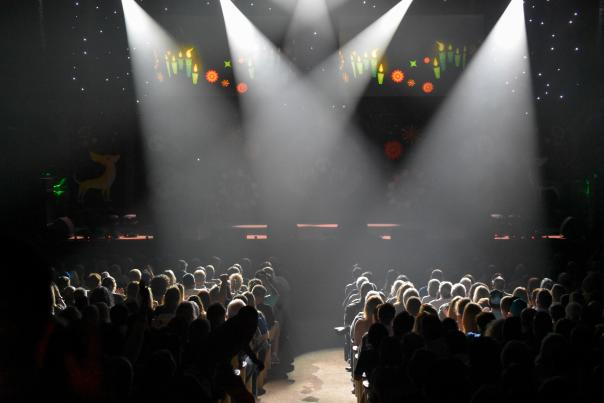 Spotlights shine on a large audience at Peabody Auditorium
