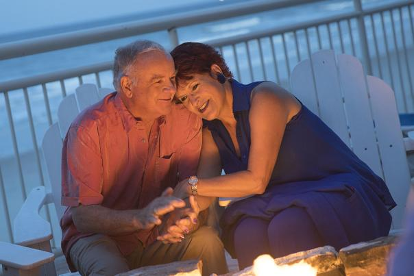 A couple enjoys a romantic evening on Daytona Beach by a firepit.
