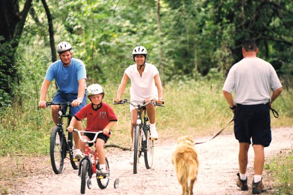 Family biking on trail passing a man walking a dog