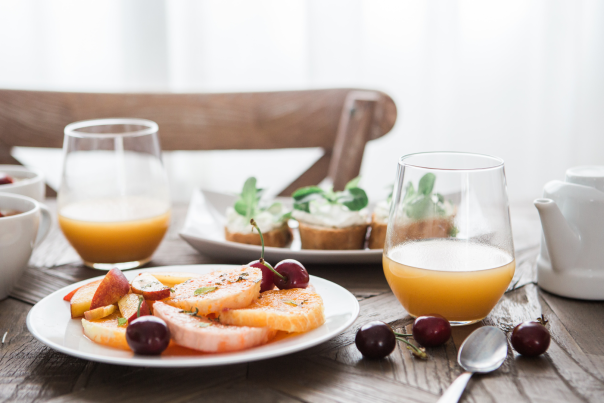 Table setting at brunch with orange juice and fresh fruit