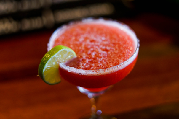 frozen pink drink with a white rim and a lime garnish