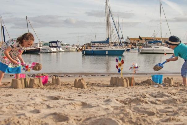 Kids building sand castles on Lyme Regis Beach
