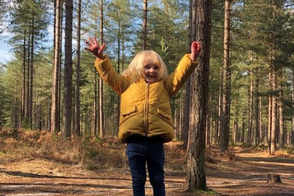 Child standing with their hands in the air in a forest in Dorset