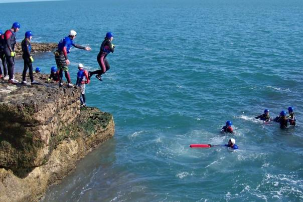 Group of people jumping into the sea part of a coasteering activity