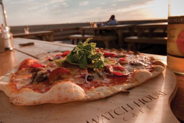 Pizza on a wooden board at Watch House Cafe, Dorset