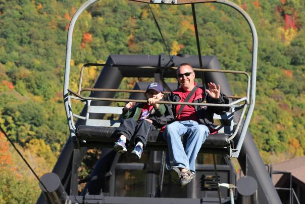 Father and son on the ski lift surrounded by fall foliage