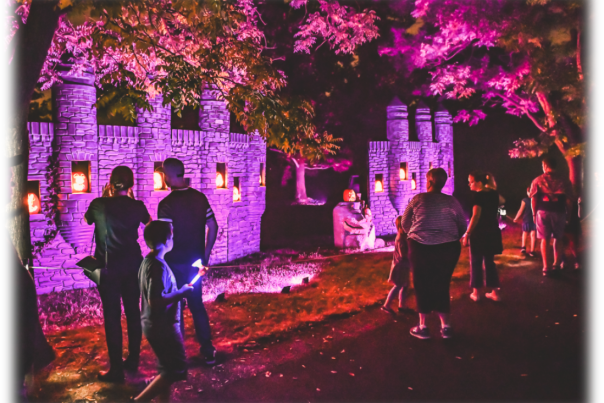Families at Lincoln Hill Farms at night, looking at jack-o'-lanterns on a castle wall
