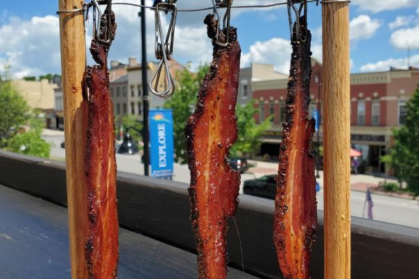 Three strips of bacon hanging on a line with clothes pins with a view of Main Street Canandaigua in the background