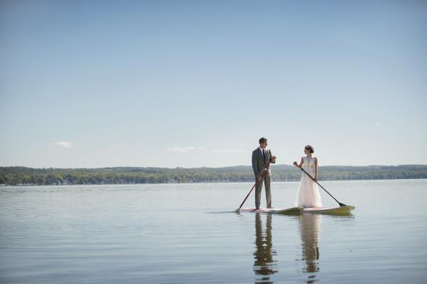 A couple paddle boarding on Canandaigua Lake
