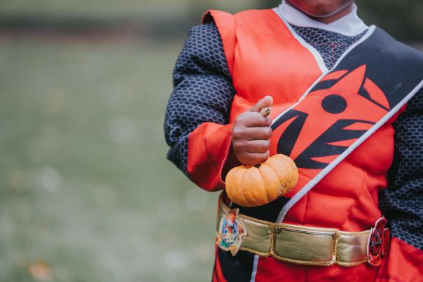 Child with costume holding pumpkin at Halloween at Applewood Estate