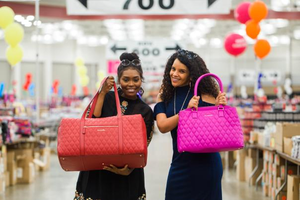 Shopping at the Vera Bradley Annual Outlet Sale group of friends holding leather travel bags