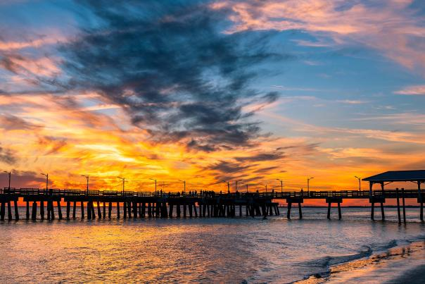 The sun sets behind the St. Simons Island Fishing Pier, a popular attraction on St. Simons Island, GA