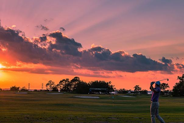 A golfer practices his drive as the sun sets over the St. Simons Sound and Sidney Lanier Bridge