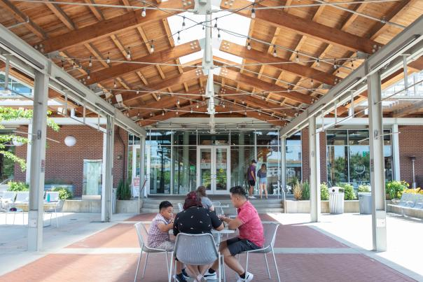 A family enjoying takeout under the pavilion at the Downtown Market Grand Rapids.