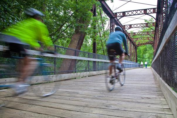 Two People Speeding Across a Bridge on Bikes