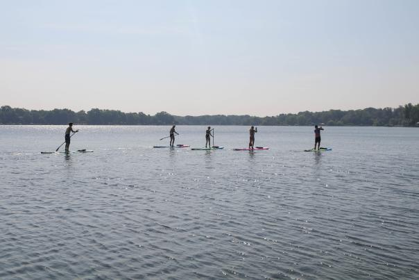 Group of 5 people stand-up paddle boarding near Grand Rapids
