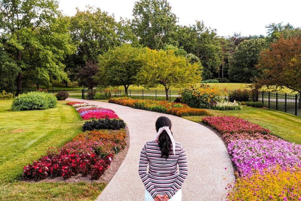 UGC - Outdoors - Attractions - Dow Gardens - Woman Looking Down Flower-Lined Path - @nrupalikulkarni