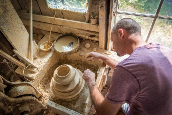 A man crafting pottery in a studio.