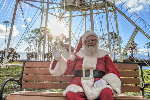 santa clause sitting on a bench in front of a lighthouse
