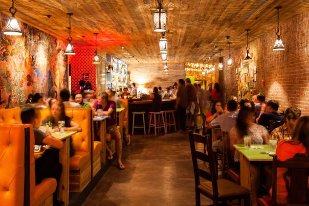People sitting in booths inside The Pastry War in Houston