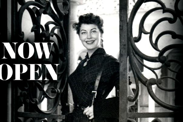 Ava Gardner walking through a metal gate with words Now Open across the image.
