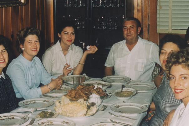 Ava Gardner and several family members seated around a dining table. Ava has a fork lifted toward her face and all are turning to look at camera.