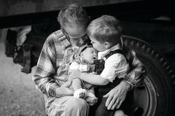 A Grandfather holding an infant Granddaughter and toddler Grandson