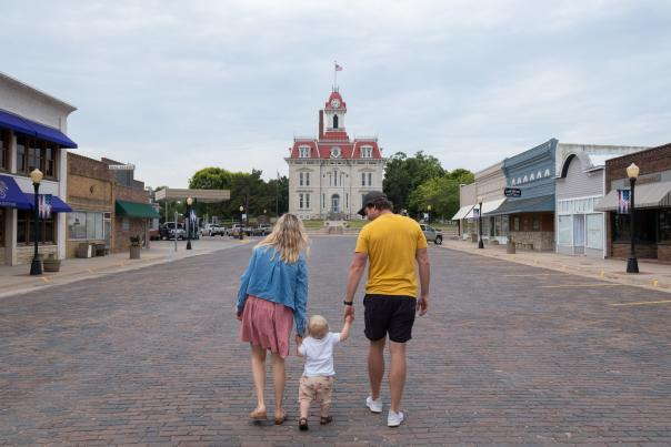 A family walks hand in hand on a brick street toward the Chase County Courthouse