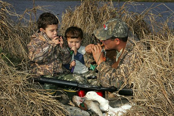 Father and Sons blowing duck calls