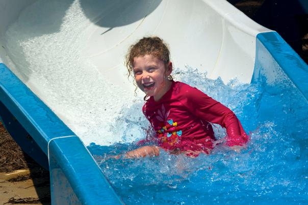 Kid on Water Slide at Sandy Beach Water Park