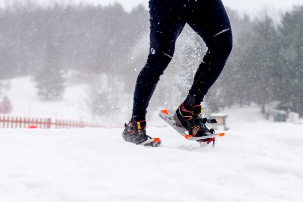 A person walking through snow in snowshoes.