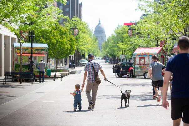 A man and child walking a dog down State Street in Madison