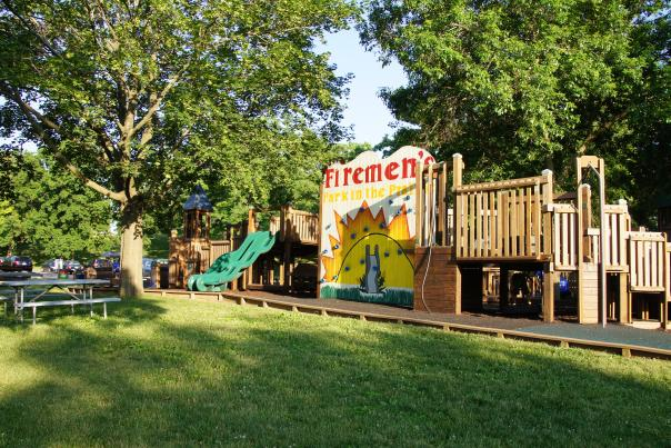 A wooden playground surrounded by trees, with a sign that says Firemen's Park in the Prairie. The sign has climbing footholds on it.