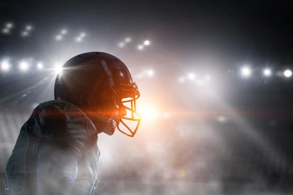 A football player stands in the bright lights of a stadium