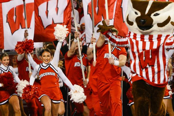 Bucky Badger and University of Wisconsin cheerleaders run onto the field