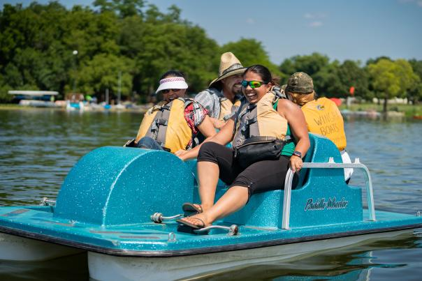 A group of four people enjoy Madison's lakes via a paddle boat