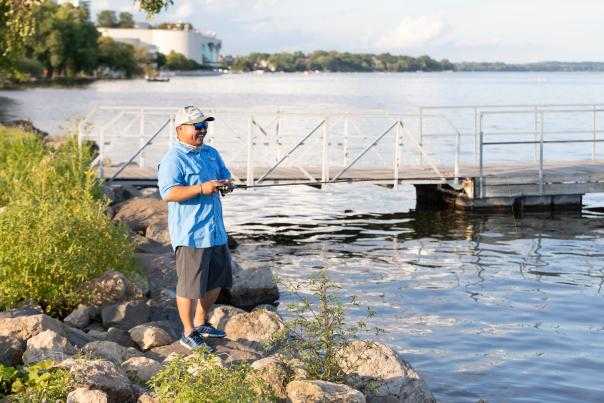 A man fishes on the rocks along Lake Monona