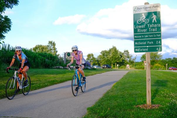 Two women ride their bikes on the Lower Yahara River Trail