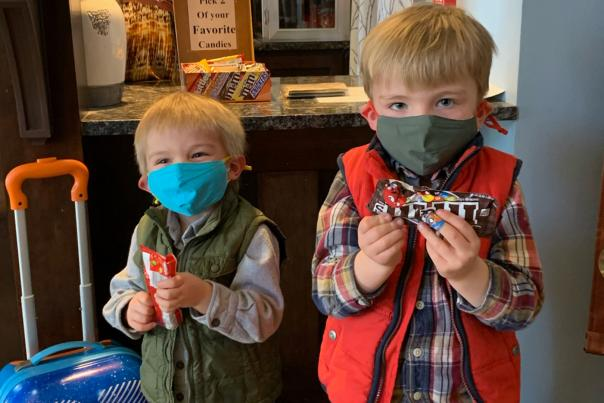 Two children wearing masks hold individual bags of candy