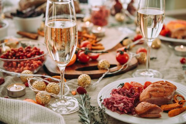 A holiday dinner table setting with glasses of champagne
