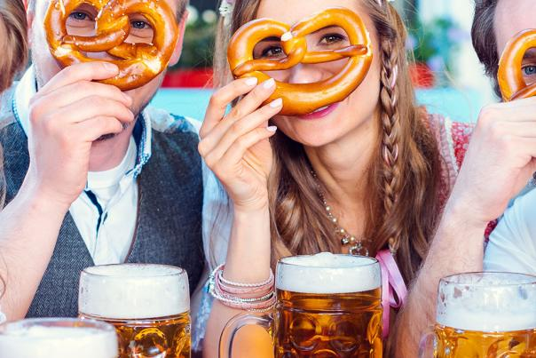 A group of friends at an Oktoberfest peer through the holes in a soft pretzel