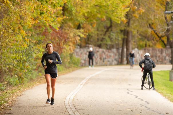 A woman runs along the paved Lakeshore Path, on a fall day. While bikers and walkers move in the background.