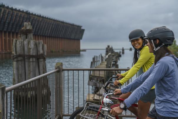 Two women on bike admiring the Lower Harbor Ore Dock.