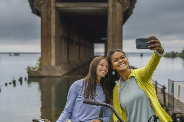 Two friends taking a selfie in front of the Lower Harbor Ore Dock in downtown Marquette