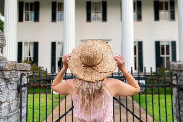 Woman looking at a historic home in Milledgeville, GA
