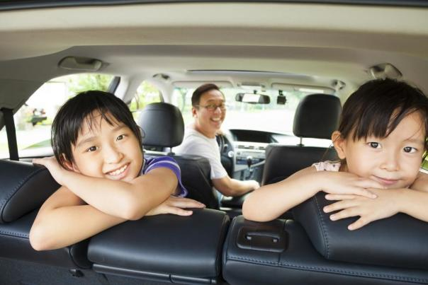 A family smiles from inside a minivan