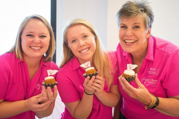 Three women wearing pink and holding cupcakes