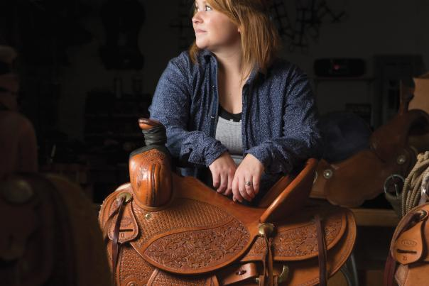 Willi Baughman leans on a saddle she made for her husband